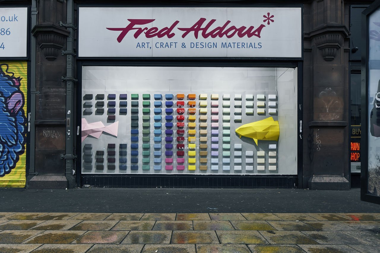 The exterior of Manchester stationery shop- Fred Aldous. Showing off their window which houses several different coloured boxes on the wall- like a rainbow spectrum. It also shows a half yellow paper fish coming in from the right and a baby pink paper fish from the left.