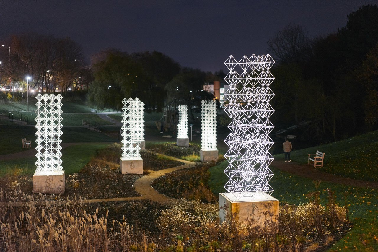 Night time shot of Seven Sisters- a exterior public art installation in Winsford park. Tall white towers made using metal hexagonal type structures