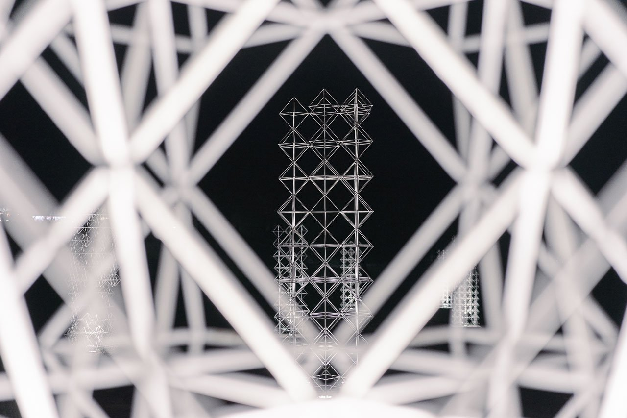 Close up look of a white steel frame sculpture. Public art by Lazerian