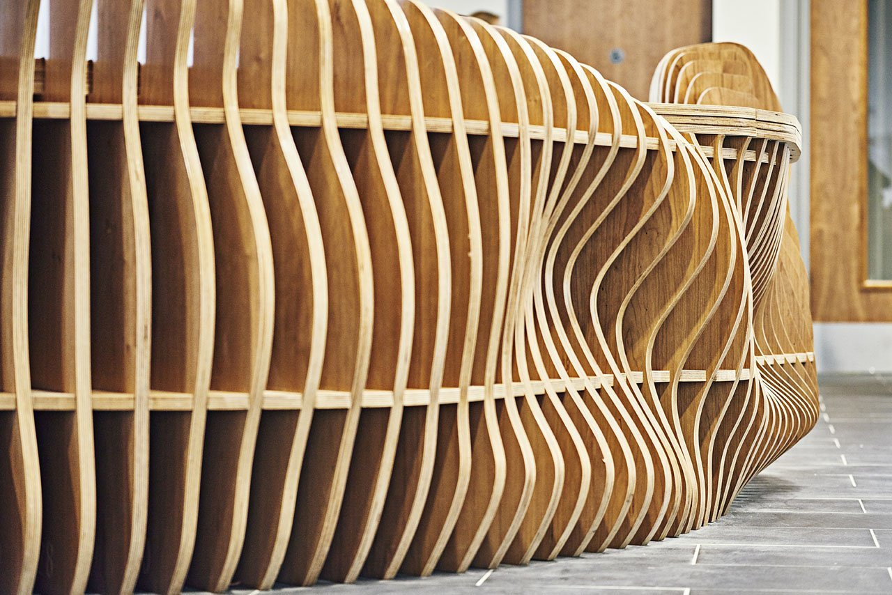 Close up side view of a contemporary wooden reception welcome desk. Focuses in on the curvy detailing of the vertical panels. Designed to represent dancers in flight.