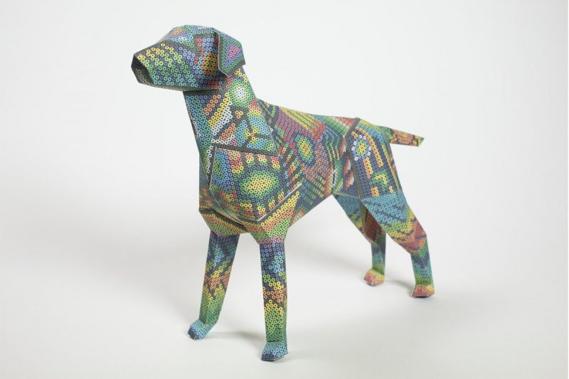 3D paper dog sculpture that has a colourful design inspired by aztecs