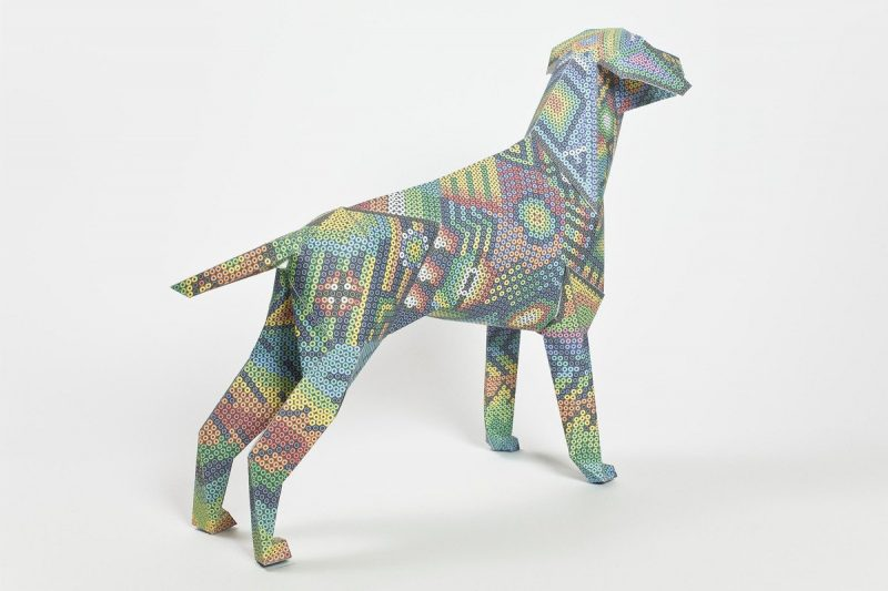 A backwards view of a paper dog sculpture with an Mexican Aztec design on its coat.