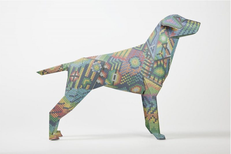 Side view of a paper dog model in 3D form. The pattern on the dog is an Aztec style with small colourful (rainbow colours) circles.