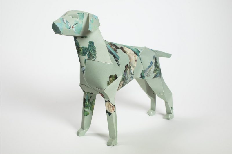 A 3D paper dog sculpture that is a light green on the background. The design on the dog is very abstract and feature different womens faces and some darker green coloured patches