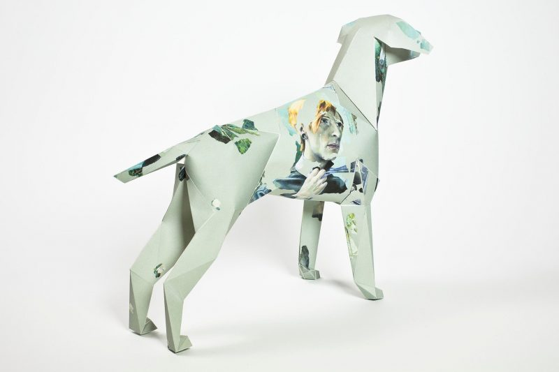 Back wards view of a paper dog sculpture in 3D form. It is light green in colour with darker green patches and a blonde masculine looking womans face drawn in a abstract style.