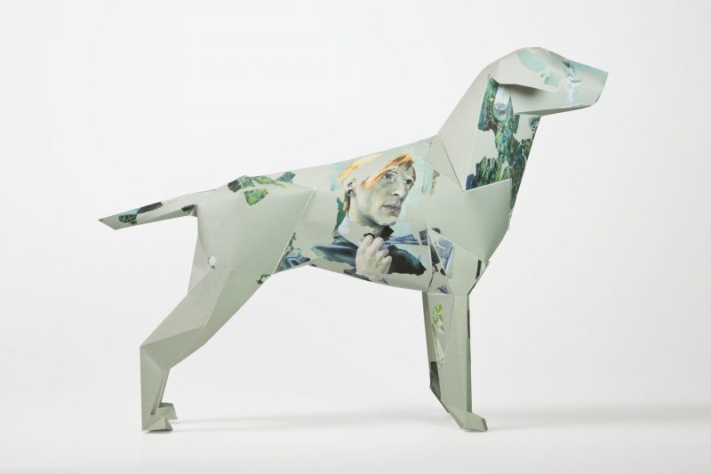 Side view of a dog sculpture made using paper. background colour is light greem with a womans face drawn in a abstract style on the dogs torso.
