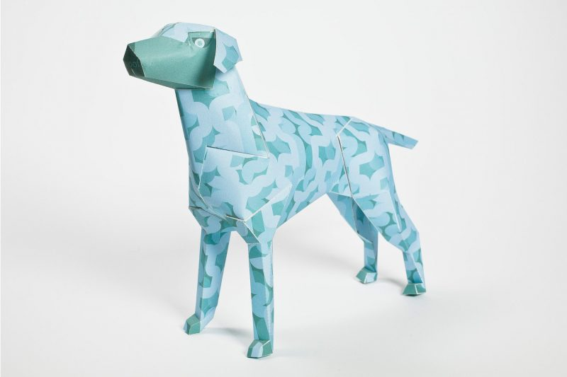 A light blue designed paper dog with wriggly fat lines all over it. The sculpture is part of a exhibition by design studio Lazerian