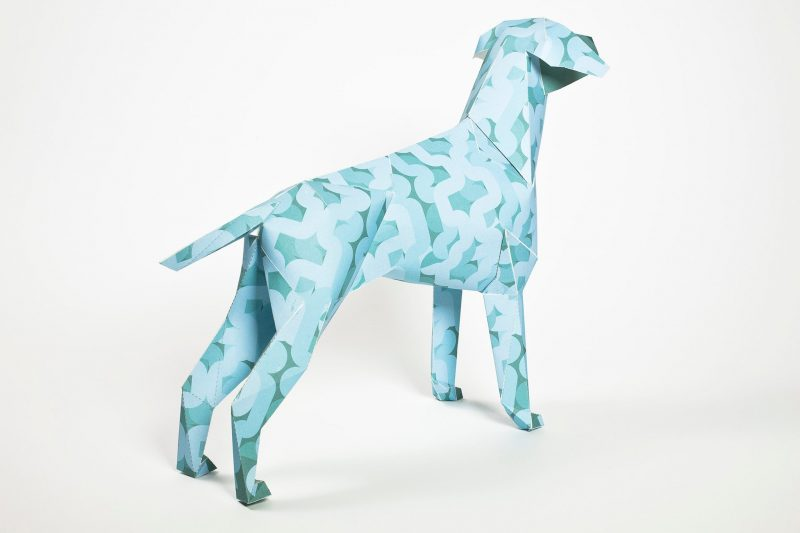 Right hand view of a light blue dog made from paper as part of a exhibition from design studio Lazerian. The design is by artist Alan Dalby