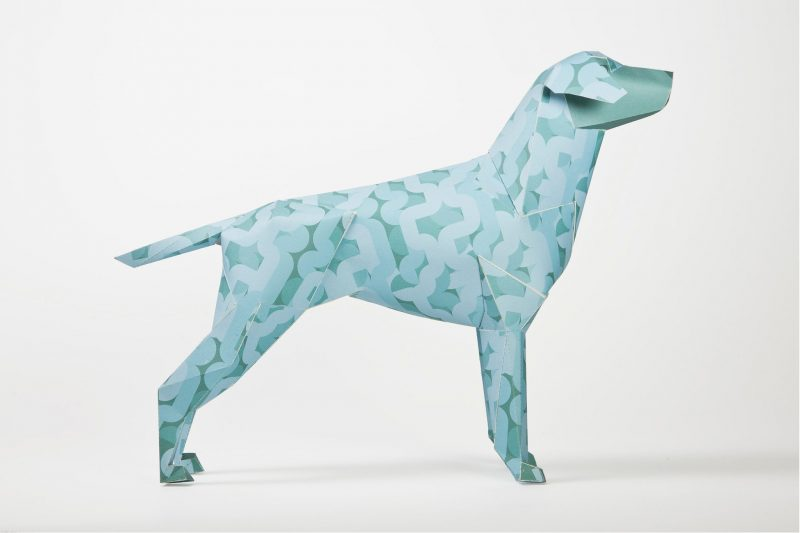 Paper dog model sculpture with a light blue design. Part of a design exhibition by design studio Lazerian. Dog coat design by Alan Dalby