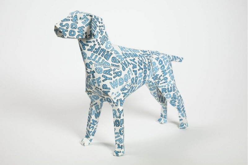 Left hand view of a paper dog model with blue bubble writing all over it. Saying words like Grrr, yap, woof etc. Part of a design exhibition from design studio Lazerian