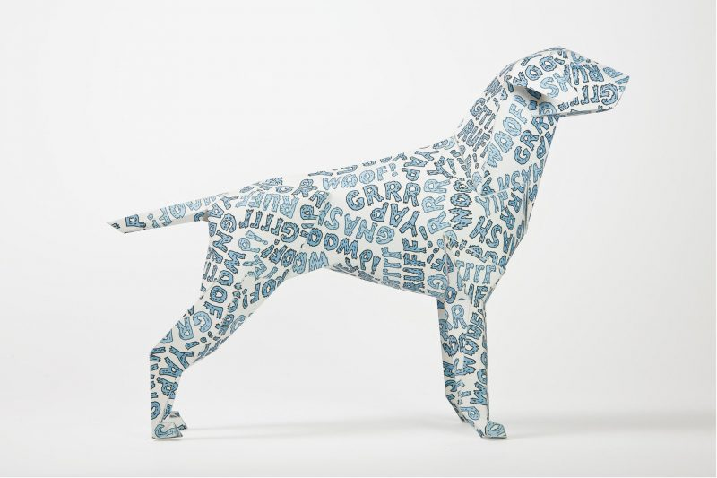 Side view of a white paper dog sculpture. Part of a design exhibition by Lazerian. The design on the dog is blue bubble writing with yap, grr, woof and ruff on it.