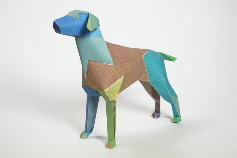 A paper dog sculpture in the colours of brown, blues and green. PArt of a Lazerian design exhibition