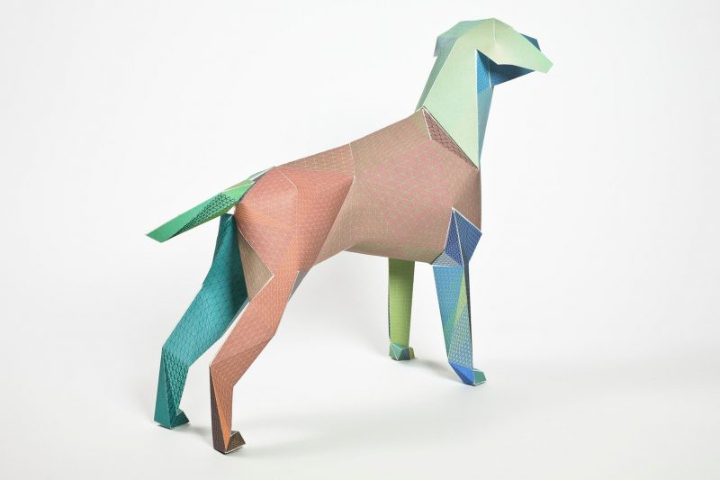 Left hand view of a paper dog sculpture. In colours green, blues and brown. Part of a deisgn exhibition by studio Lazerian.