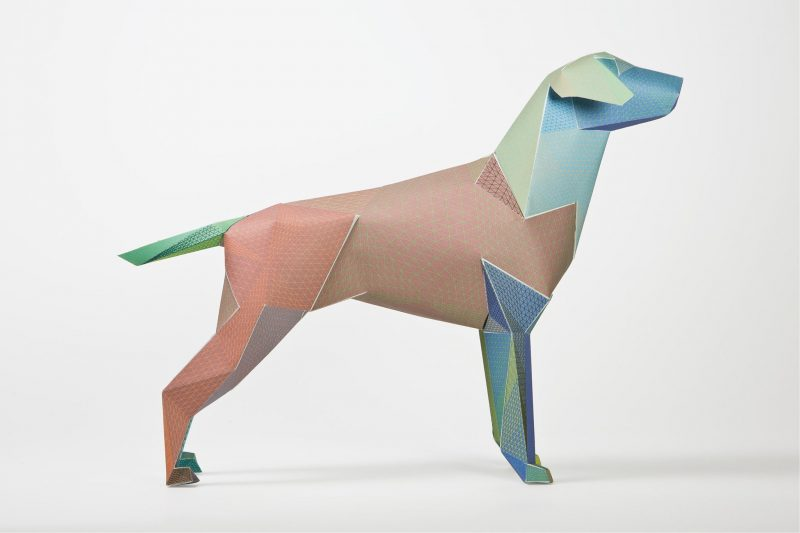 Side view of a dog model made from paper. Part of the gerald dog exhibition where designers and artists design the coats of the dogs. This one is coloured green, brown and blue.