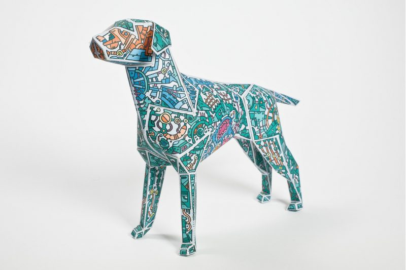 A paper dog model sculpture with a green design with lots of mechnical style drawingdoodles all over it. DEsign by Barney Ibbotson and Lazerian. Part of a Lazerian exhibition