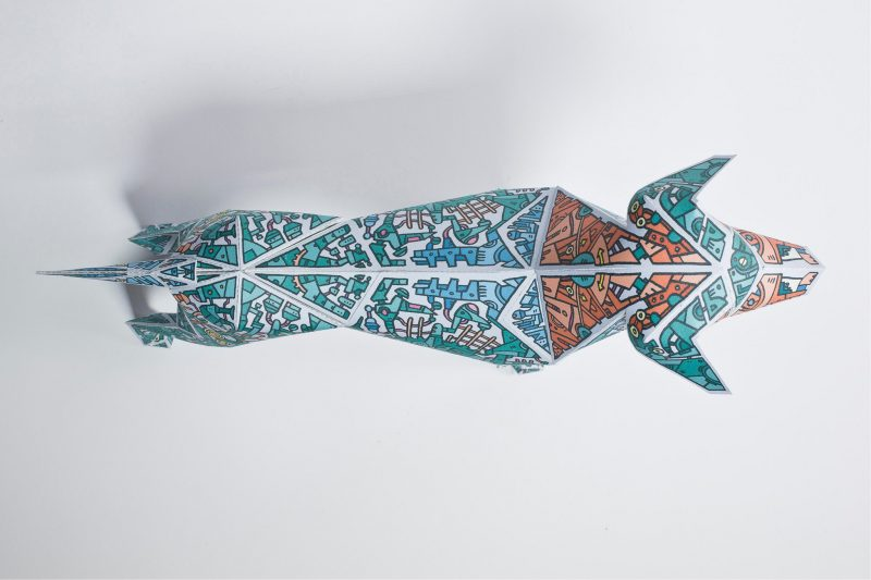 Over head view of a paper dog model. Its blue with several doodles of mechnical style tools and equipment on it.