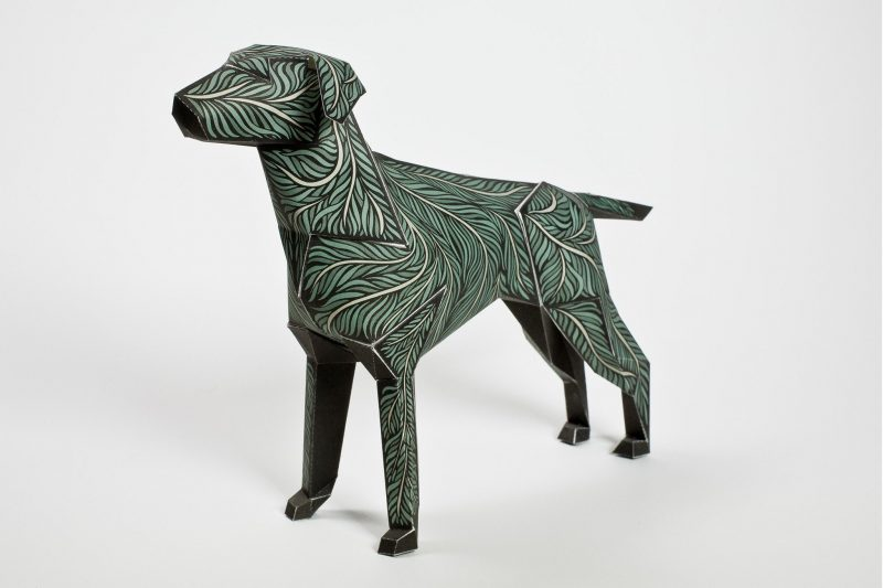 Paper dog sculpture made using paper with a green leaf design on it. For a exhibition design studio Lazerian