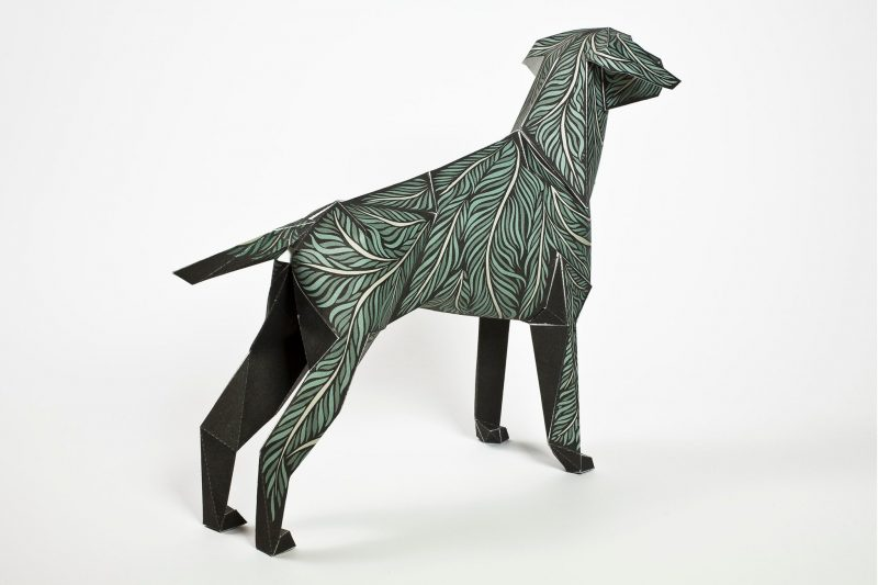 Left hand view of a paper dog model sculpture with a design of green leaves all over it. Designed for an exhibition from design studio Lazerian
