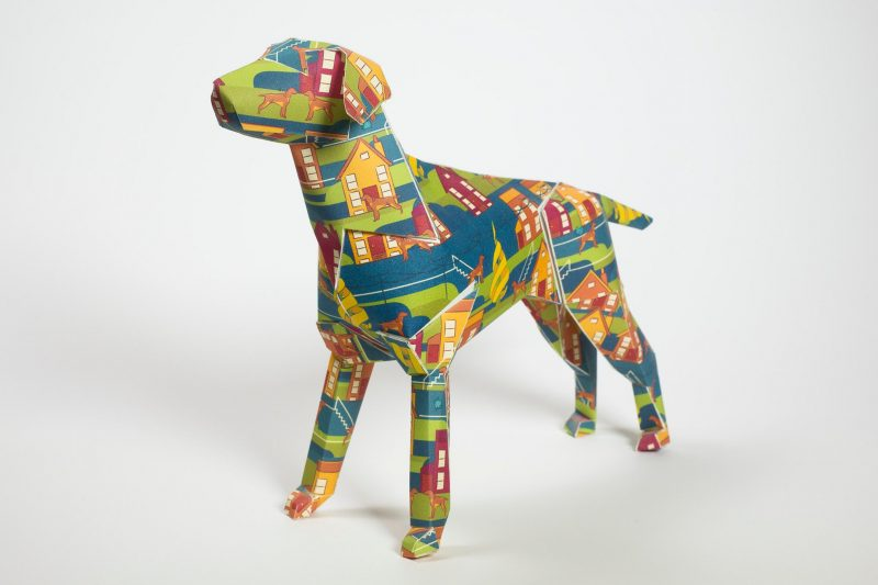Paper dog model with a colourful design. The design is red orange and yellow houses. Part of a design exhibition by Lazerian