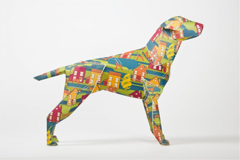 Side view of a paper sculpture of a dog which is part of a design exhibition by studio Lazerian. The designs on the coat are yellow, orange and red houses.