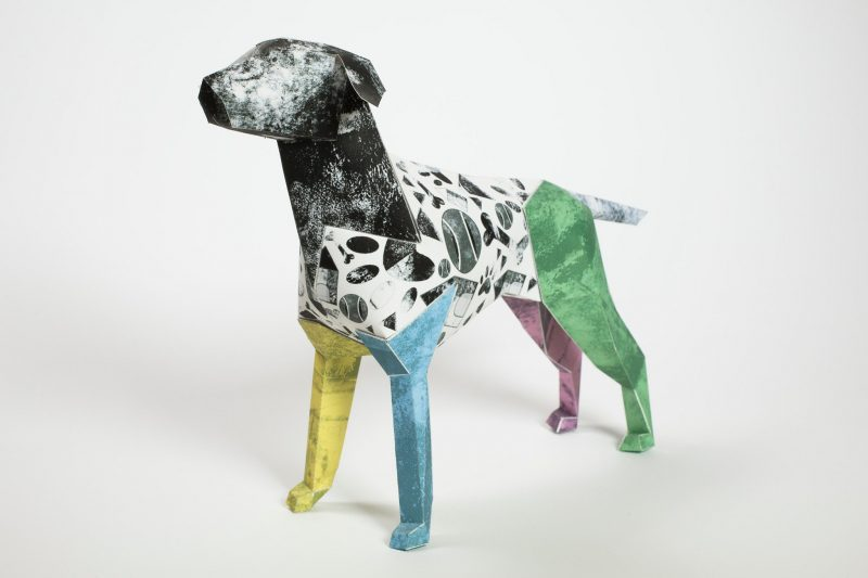 Right hand view- Gerald the paper dog sculpture for an international design exhibition by LAzerian. Design by Caitlin Totten. The design has different coloured legs (yellow, blue, green and purple)