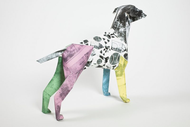 Left hand view- paper dog model with the design from artist Caitlin Totten for exhibition by design studio Lazerian. The design on the dog has colourful legs that are yellow, purple, blue and green.