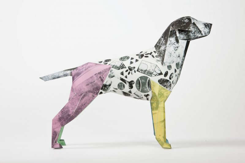 Paper dog model sculpture. PArt of a design exhibition by Lazerian. Artist Caitlin Totten designed a pattern on the dog with 4 different coloured legs- purple, green, yellow and blue.