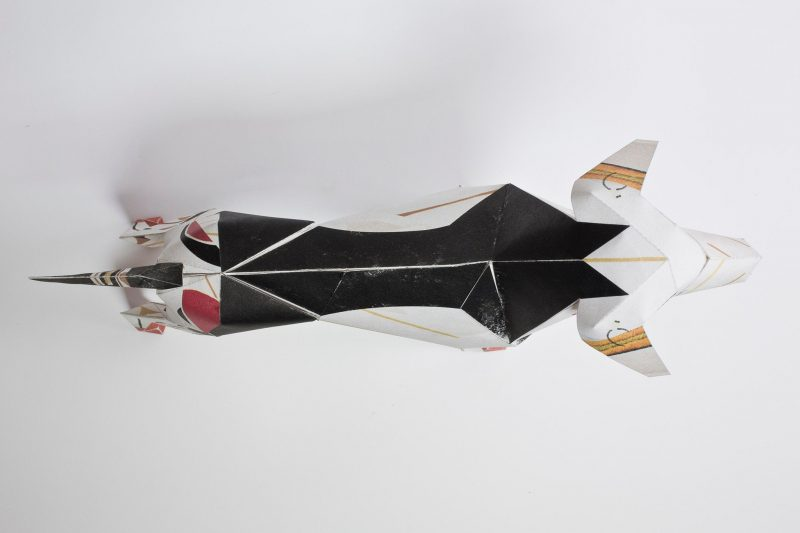 Over head view of a paper dog sculpture design and as part of a exhibition by design leaders LAzerian. The pattern on the coat makes the paper dog look like a butler. It was designed by Christos Kourtoglou