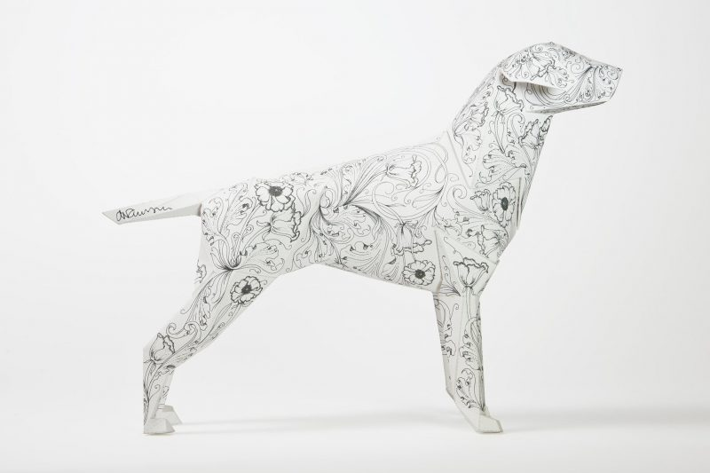 A side view of a paper dog sculpture for a design exhibition by Lazerian. The paper dog model has a repeating flower pattern by artist Daren Newman