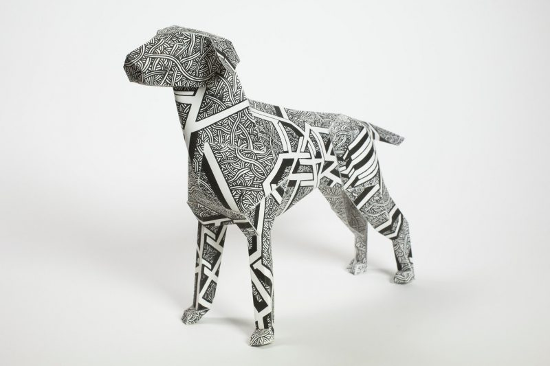 A paper dog model sculpture by artist Dave Bain. PArt of an exhibition by design studio Lazerian. The dog has a black and white pattern