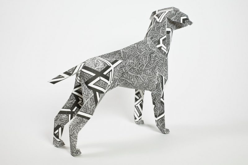 A back view of a paper dog sculpture as part of the exhibition by design studio Lazerian. The dog has a black and white coat designed by Dave Bain