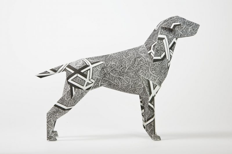 Side view of a paper dog sculpture which is black and white in design. Designed as part of a exhibition by design studio Lazerian and Dave Bain