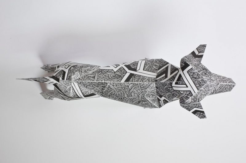 Overhead view of a paper dog model that is black and white in colour and design. The designwork is by Dave Bain and is part of an exhibition by design studio Lazerian.