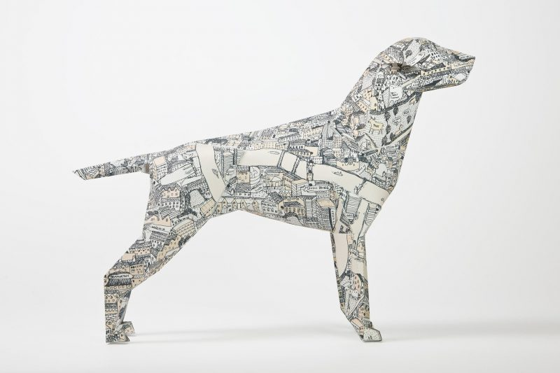 Side view of a paper dog model with a map pattern all over it. Part of a exhibition by design studio Lazerian