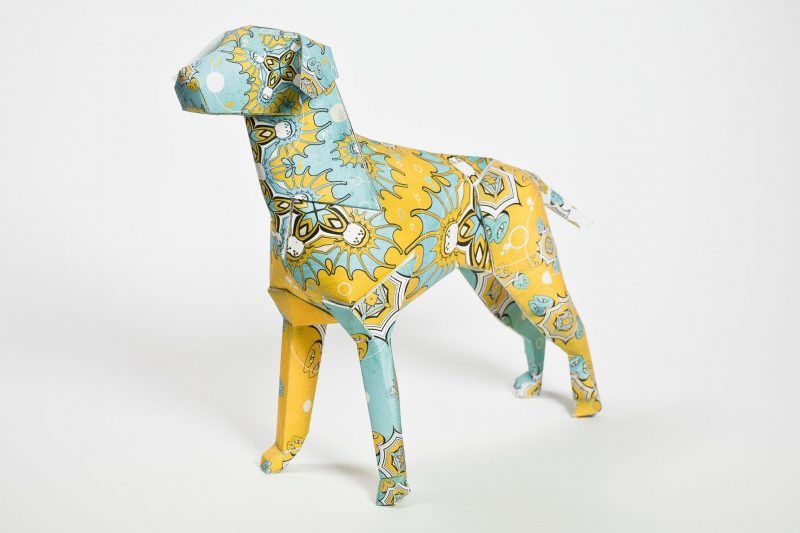 A paper dog sculpture with a design on its coat. The design is influenced by indian patterns and is yellow and mint green. Part of a international design exhibition by world renown design leaders Lazerian.