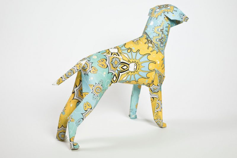 Back view of a paper dog sculpture. As part of a international design exhibition by designer leaders Lazerian. The design on the dog resembles an Indian style pattern in colours of mint green and yellow.