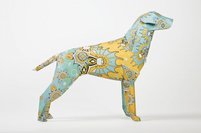 A paper dog model from a international exhibition by design studio Lazerian. A different artist was invited to out their own design on the paper dog sculpture. this one is blue and yellow and inspired by the artists time in Egypt. The artist is DBO Dave Bowcutt and he created a repeating pattern of Egyptian lanterns
