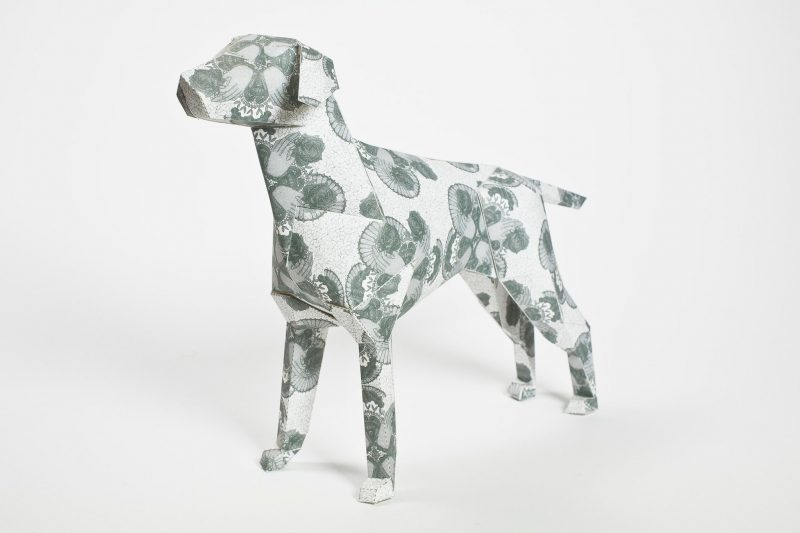 A paper dog sculpture with a simple lace pattern on it in a light grey colour. On closely inspection you can see the elements are hand drawn. Part of an international design exhibition by design leaders Lazerian. The artist who created the design on the dog is Deborah Ballinger