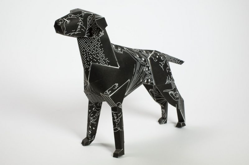 A black paper dog model by designers DED. The design is inspired by black magic mixed with 1950's colouring books. The pattern consists of white rabbits and faces drawn on it as a white line pattern. Part of an international exhibition by Lazerian.
