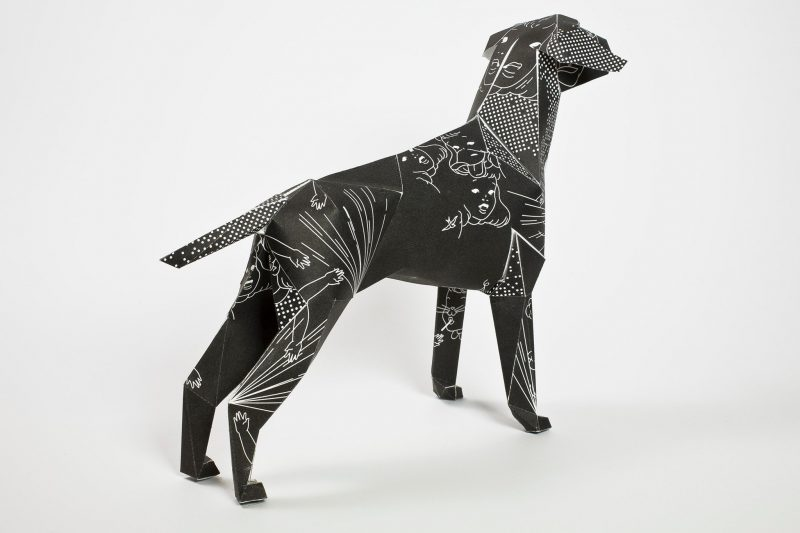 A back view of a black paper dog 3D sculpture. The dog was created by designers DED and is inspired by black magic and 1950's comics. It has white line drawings of faces and animals.