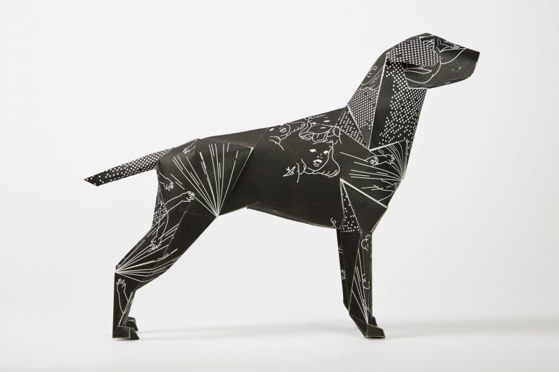 Side view of a black paper dog model in the form of a 3D sculpture. The dog has a design on its coat inspired by 1950's comics and black magic and consists of white line drawings of rabbits and ladies faces. The design was done by DED for the international exhibition by leading designers Lazerian