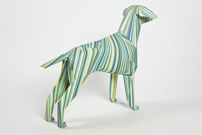 A paper dog model of a 3D sculpture. Part of a design exhibition by lazerian. The design on the dog consists of different shades of greens, yellows and greys all in a verticcal lines going down the body.