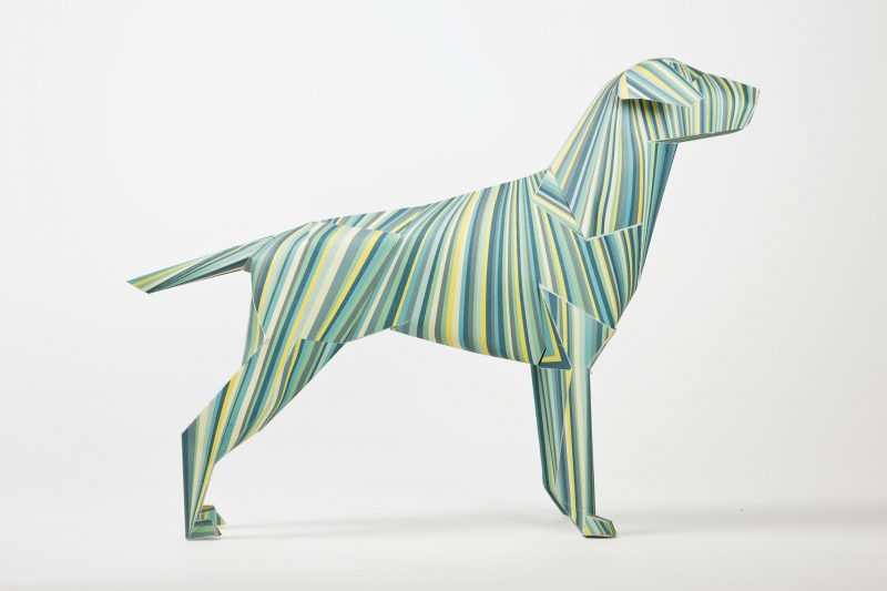 Side view of a 3D paper dog model. The design on the dog has vertical lines coloured in different types of greens, yellows, greys placed sporadically.