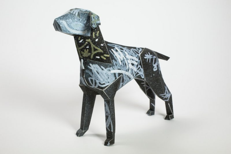 A paper dog model in the form of a 3D sculpture created by Dr Me as part of a exhibition by design studio Lazerian. The design consists of a spray paint like silver graffiti on a black dog