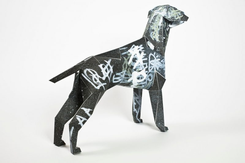Back view of a black paper dog sculpture with silver graffiti sprayed across it. The design is by artist and designers Dr. Me as part of a design exhibition by Lazerian