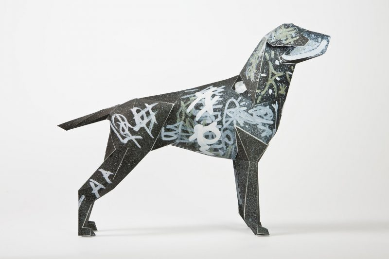 Side view of a black 3D dog sculpture with silver graffiti scrawled all over it. Part of an international exhibition by designers Lazerian. The design on the dog was created by Dr.Me
