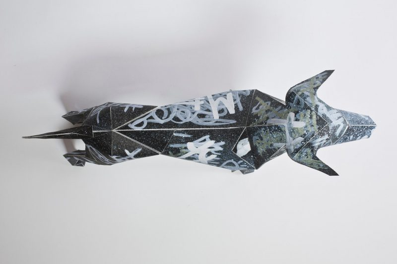 Over head view of a black paper dog model in a 3D model form with silver graffiti scrawled all over it. Part of a exhibition by designer studio Lazerian. Several artist and designers were asked to put their own creation on the dogs. This dog is by designers and artist Dr.Me