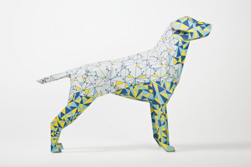 Side view of a white paper dog model in 3D form. the dog is part of an international design exhibition by design studio lazerian. Several artist and designers were invited to customise the dogs in their own style. This dog is from Eskimo Creative. It consists of several lines connecting to make smaller traingles of all different shaoes and sizes. On the legs and face the traingles are all filled with a mixture of yellow and blue in colour.