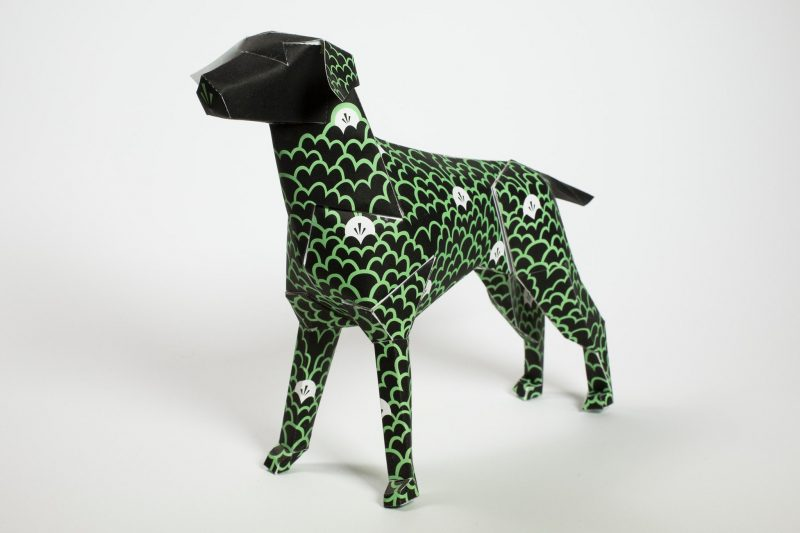 Paper dog sculpture in 3D form. Part of an exhibition by design studio lazerian. Artist and designers were all invited to customise the dog in their own creative styles. This dog is all black with green line formations that look like clouds. Intermediately dotted over the body are filled white clouds. The dog was designed by G87