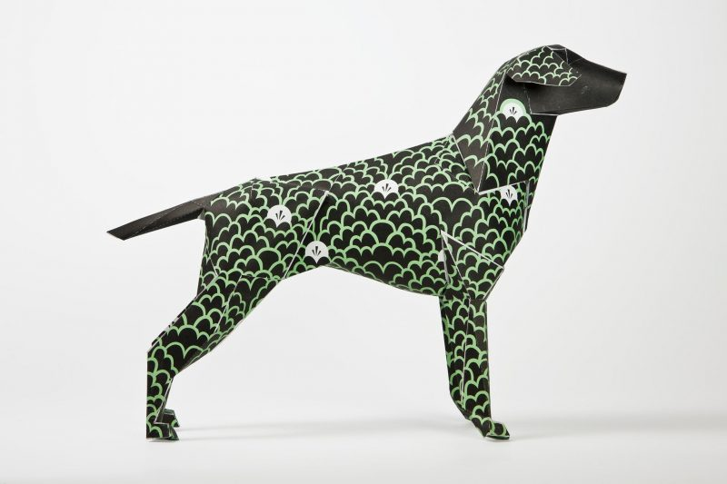 Side view of a black paper dog sculpture. Decorated by artist G87 with green linear bump forms that are inspired by clouds. Also on the model form are individually filled white clouds. The paper sculpture is part of an exhibition by design studio Lazerian where designers and artist from around the world were all invited to customise the Lazerian dog logo with their own unique signature styles.